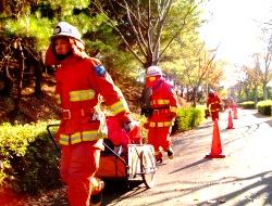 中継送水を行うために可搬ポンプを搬送する職員と消防団員